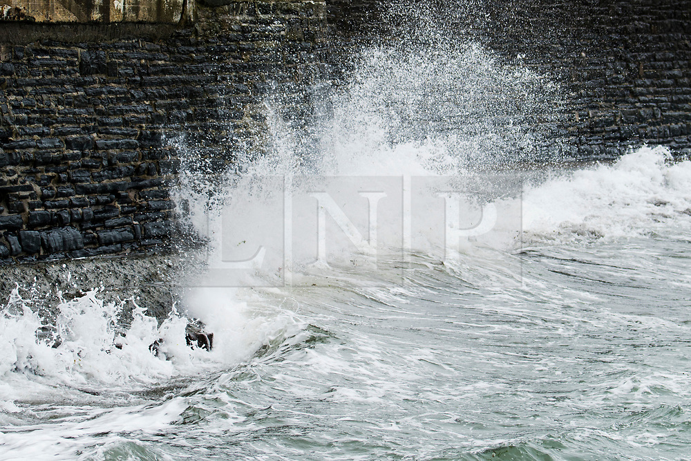 © London News Pictures. 14/04/2017 Aberystwyth, UK.<br /> A wave crashes on to the seafront promenade on a dreary, cold grey and damp Good Friday morning in Aberystwyth on the Cardigan Bay coast of west Wales UK at the start of the Easter Bank Holiday weekend. Photo credit: Keith Morris/LNP