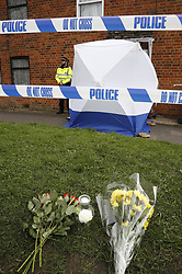 © Licensed to London News Pictures. 15/03/2017. Faringdon, UK. Floral tributes are left outside a house after a child was found dead. Thames Valley police said a woman has been arrested on suspicion of murder after they found the body of a child at a property at Bromsgrove Cottages in Farringdon  yesterday lunchime.   Photo credit: Peter Macdiarmid/LNP