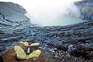 A basket of mined sulphur amidst the alien landscape by the crater lake at the Kawah Ijen Sulphur Mines in East Java, Indonesia, Southeast Asia