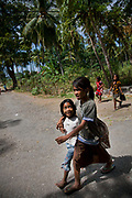 Two girls are on their way home from school on  the island Atauro.  Atauro is an island with 10.000 inhabitants belonging to the state of Timor Leste, 25 km north of the capital Dili. Timor Leste gained independence from Indonesia in May 2002.