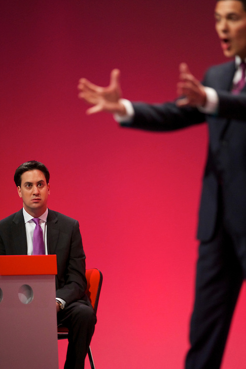 As newly elected Labour leader and younger brother, Ed Miliband, looks on David Miliband delivers a speech to delegates attending the Labour Autumn Conference in Manchester on 27 September 2010.