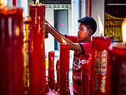 13 JULY 2017 - BANGKOK, THAILAND: A boy scoops molten candle wax out of prayer candles at Chao Mae Thapthim Shrine in the Dusit district of Bangkok. The Chinese shrine is at the foot of Krung Thon Bridge and serves poor communities along the Chao Phraya River. The shrine is along a part of the riverfront the government wants to tear down to build an esplanade. The future of the shrine itself is unknown, but many of the communities around it could be evicted and razed.         PHOTO BY JACK KURTZ