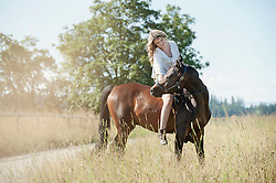 Young woman riding a horse on meadow, Bavaria, Germany