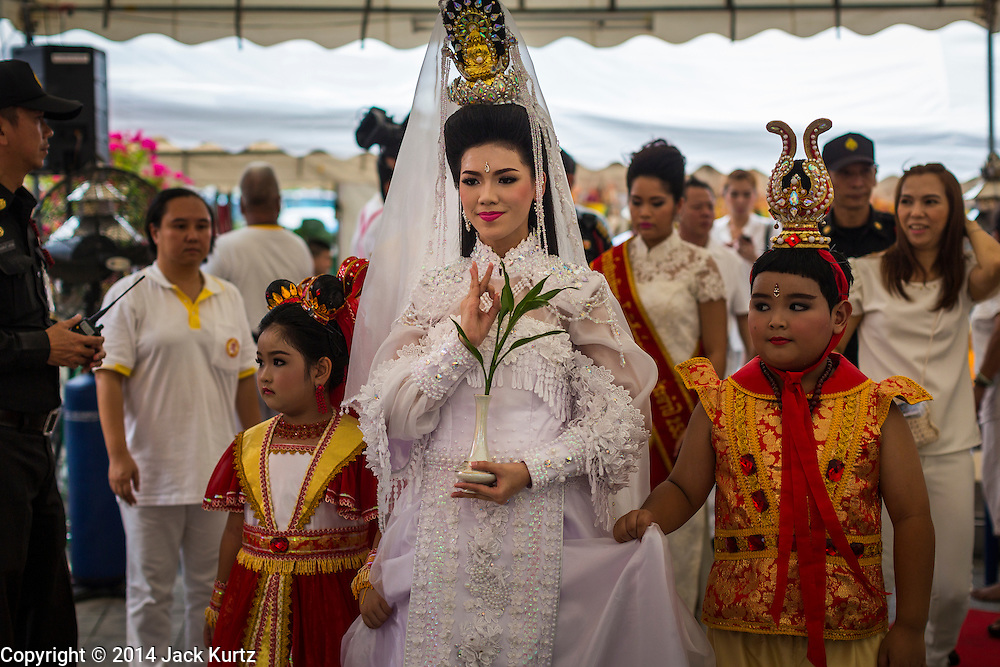 24 SEPTEMBER 2014 - BANGKOK, THAILAND: A woman dressed as Guanyin, the Chinese Goddess of Mercy, leads a procession before the Vegetarian Festival Parade in Bangkok. The Vegetarian Festival is celebrated throughout Thailand. It is the Thai version of the The Nine Emperor Gods Festival, a nine-day Taoist celebration beginning on the eve of 9th lunar month of the Chinese calendar. During a period of nine days, those who are participating in the festival dress all in white and abstain from eating meat, poultry, seafood, and dairy products. Vendors and proprietors of restaurants indicate that vegetarian food is for sale by putting a yellow flag out with Thai characters for meatless written on it in red.    PHOTO BY JACK KURTZ