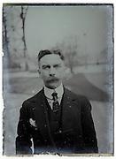 man standing under the Eiffel tower 1900s