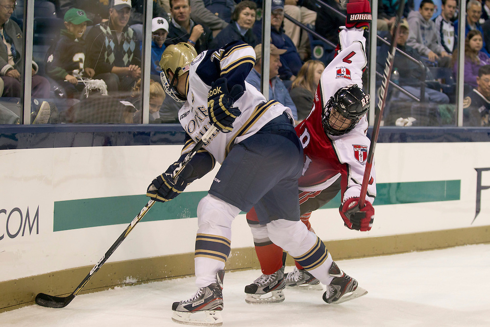 Notre Dame defenseman Kevin Lind (#25) and RPI forward Zach Schroeder (#7) battle on the boards in first period action of NCAA hockey game between Notre Dame and Rensselaer Polytechnic Institute (RPI).  The Notre Dame Fighting Irish defeated Rensselaer Polytechnic Institute (RPI) Engineers 5-2 in game at the Compton Family Ice Arena in South Bend, Indiana.