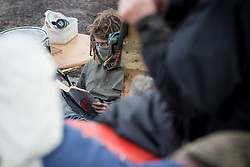 © Licensed to London News Pictures . 21/03/2014 . Barton Moss , Manchester , UK . A protester at the camp reads Understanding Power by Noam Chomsky . The Barton Moss anti-fracking demonstration camp today (Friday 21st March 2014) . Photo credit : Joel Goodman/LNP