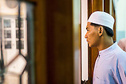 09 JULY 2013 - PATTANI, PATTANI, THAILAND:  A man looks out a window at Pattani Central Mosque in Pattani, Thailand, Tuesday night on the first night of Ramadan. Ramadan is the ninth month of the Islamic calendar, and the month in which Muslims believe the Quran was revealed. Muslims believe that the Quran was sent down during this month, thus being prepared for gradual revelation by Jibraeel (Gabriel) to the Prophet Muhammad. The month is spent by Muslims fasting during the daylight hours from dawn to sunset. Fasting during the month of Ramadan is one of the Five Pillars of Islam.   PHOTO BY JACK KURTZ