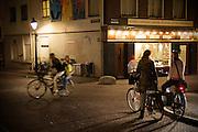 Op de Oudegracht in Utrecht praten twee vrouwen 's avonds laat nog even met elkaar op de fiets voor ze afscheid nemen. Ondertussen rijden een fietser met iemand achterop voorbij.<br /> <br /> In the late evening two women are saying goodbye at the Oudegracht in Utrecht on their bikes. Meanwhile a cyclist is passing by with a passenger at the back of the bike.