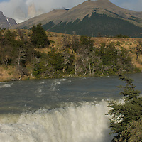 The Paine River pours over Paine Falls under  the Towers of Paine in Torres del Paine National Park, Chile
