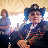 93-year-old WWII veteran John K. Yazzie sits with a large crowd to watch the 8th Annual All Veterans Gourd Dance in Twin Lakes Sept. 17.