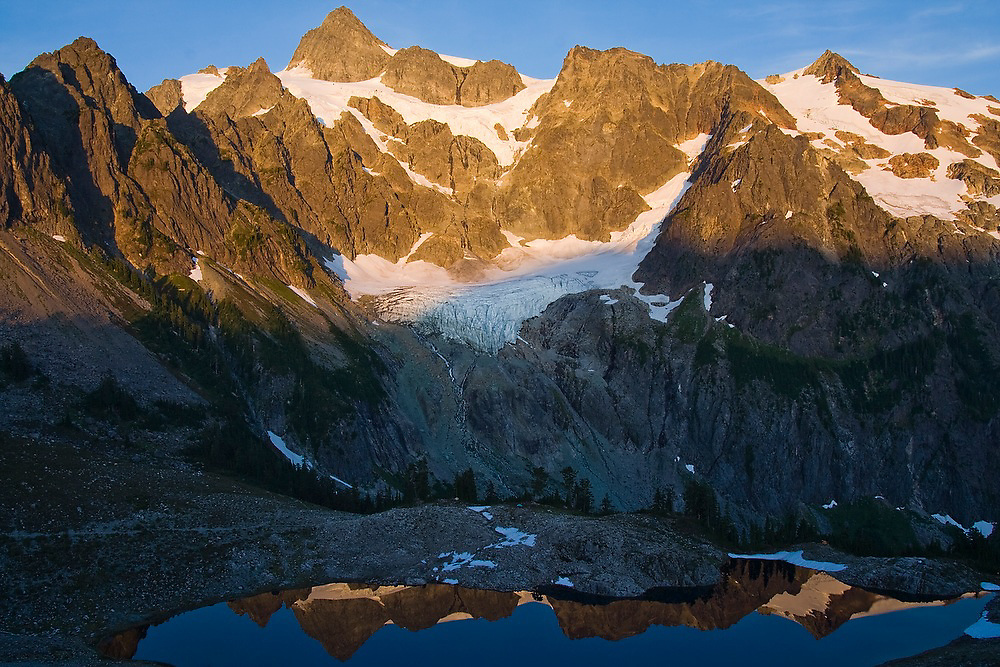 Mount Shuksan illuminated at sunset and reflected by Lake Ann below, Mount Baker-Snoqualmie National Forest, Washington.