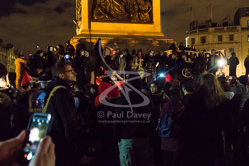 London, November 05 2017. Anti-capitalists gather in Trafalgar Square, London for the annual 'Million Mask March' which happens on November 5th every year, with many of the protesters donning 'V' For Vendetta Guy Fawkes masks. Past marches have turned violent with police horses shot by fireworks and police vehicles burned. PICTURED: Protesters on the base of Nelson's column in Trafalgar Square. © Paul Davey