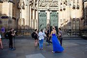 "A ""just married"" couple getting photographed in front of St. Vitus Cathedral in Prague. The house of worship is a Roman Catholic metropolitan cathedral on the area of the Prague Castle complex and the seat of the Archbishop of Prague."