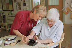Clinic assistant showing elderly woman how to use a hole punch to make Christmas cards during occupational therapy session,