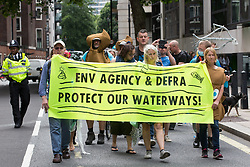 London, UK. 5th August, 2021. Extinction Rebellion activists arrive outside the Department for Environment, Food and Rural Affairs (Defra) to protest against the pollution of the UK's waterways. The activists were highlighting pollution of rivers by water companies and farms and the failure of the Environment Agency and Defra to protect waterways and to prosecute offenders.