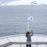 A guest on the bow of the National Geographic Explorer takes photos with her iPhone while navigating near the South Shetland Islands, Antarctica.