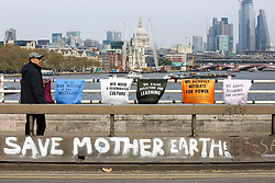 "© Licensed to London News Pictures. 18/04/2019. London, UK. A man walks past ""Save Mother Earth"" written on the side of the Waterloo Bridge as environmental activists demonstrates on the fourth day of an ongoing climate change protest to demand decisive action from the UK Government on the environmental crisis. Photo credit: Dinendra Haria/LNP"