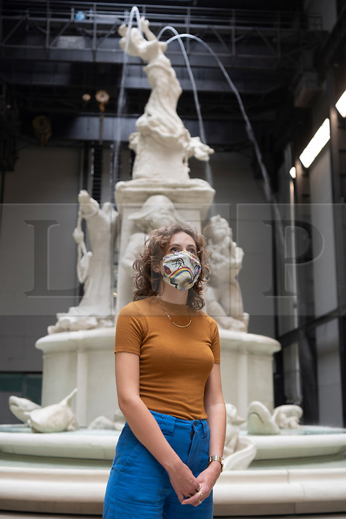 """© Licensed to London News Pictures. 24/07/2020. London, UK. A Tate staff member wearing a face mask poses next to """"Fons Americanus"""", 2019, by Kara Walker. , at the Tate Modern art museum. The Tate Modern will re-open to the public after closing due to the Coronavirus outbreak. Photo credit: Ray Tang/LNP"""