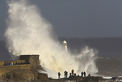 © Licensed to London News Pictures. 03/02/2017<br /> <br /> People stand on the rocks as huge waves strike the harbour wall and lighthouse at Porthcawl, south Wales, as strong winds and heavy rain batters Britain during storm Doris, with gusts reaching up to ninety miles per hour in places, Friday 23 February 2017.<br /> <br /> Photo credit: Geoff Caddick/ LNP