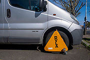 A bright yellow DVLA wheel clamp on a vehicle in a car park on the 13th of May 2021 in Folkestone, Kent, United Kingdom. The DVLA use automatic number plate readers to locate untaxed vehicles on the streets and clamps them until tax and fines have been paid. A clamped vehicle cannot be moved until it is removed.