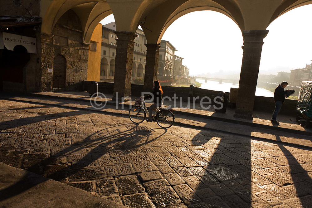 """An Italian commuter cycles on her bike across the central arches of the Ponte Vecchio over the River Arno in Florence. It is early on an autumnal morning and only two figures are seen but within a few hours this world famous tourist landmark will be teeming with visitors from around the world, their international languages heard across this location. In the background we see the still waters of the Arno and riverside buildings including the Uffizi on the left. The Ponte Vecchio (""""Old Bridge"""") is a Medieval bridge over the Arno River, in Florence, Italy, noted for still having shops built along it, as was once common. Butchers initially occupied the shops; the present tenants are jewellers, art dealers and souvenir sellers. It has been described as Europe's oldest wholly-stone, closed-spandrel segmental arch bridge"""