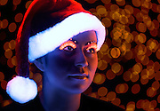 Young woman wearing a glowing Christmas stocking hat and glowing eyelashes against a filed of soft lights.Black light