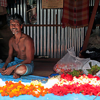 Asia, India, Calcutta. Happy flower vendor in the flower market in Calcutta.