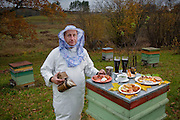 Aivars  Radzins, a forester and beekeeper, wearing his bee-kleeping clothes, with a smoker and his typical day's worth of food in his backyard in Vecpiebalga, Latvia. (From the book What I Eat: Around the World in 80 Diets.) MODEL RELEASED.