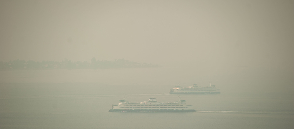 2018 AUGUST 20 - Two Washington State Ferry ships sail on Puget Sound off Alki as smoke fills the skies of Seattle, WA, USA. By Richard Walker