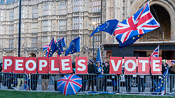 "© Licensed to London News Pictures. 11/12/2018. LONDON, UK. Steve Bray, founder of SODEM (Stand Of Defiance European Movement), stands amidst signs showing the words ""Peoples Vote"" which are held up outside the House of Commons by anti-Brexit demonstrators. Theresa May, Prime Minister, is touring European capitals to try to renegotiate the Brexit agreement with the European Union after today's meaningful vote by MP's was deferred.  Photo credit: Stephen Chung/LNP"