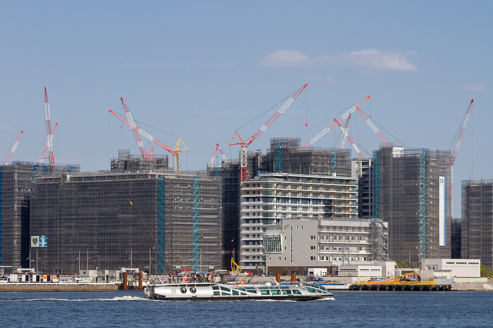A distinctive Himiko tour boats crossing in front of the construction site of the Tokyo 2020 olympic Village. Tokyo, Japan. Monday April 15th 2019