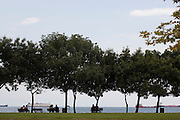 People take shade under the trees in Istanbul and watch enormous tankers move to and from the Turkish capital's port...Istanbul 7 June 2012