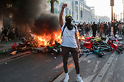 Protester, with fist salute, with burning barricades of bicycles. Black tuesday commemoration of the deaths of Adama Traore in France and George Floyd in USA. Tribunal de Paris, Paris, June 2, 2020. Photography by Nigel Dickinson/Hans Lucas.<br /> Manifestant, avec le premier coup de poing, avec des barricades brulantes de velos. Mardi noir commemoration de la mort d Adama Traore en France et de George Floyd aux Etats-Unis. Tribunal de Paris, Paris, 2 juin 2020. Photographie par Nigel Dickinson/Hans Lucas.