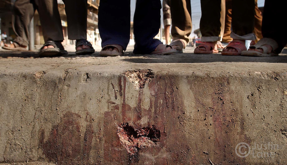 The feet of a group of boys are seen gathered around a piece of sidewalk that was damaged and bloodied by a mortar explosion on Thurday night in the town of Baqubah, Iraq. 7 Iraqis were killed in the blast; It is not known who conducted the attack.