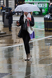 A woman crosses the wet pavement at Piccadilly Circus. As forecasters predicted, the rain arrives in London where Londoners and tourists go about their business. London, February 13 2018.