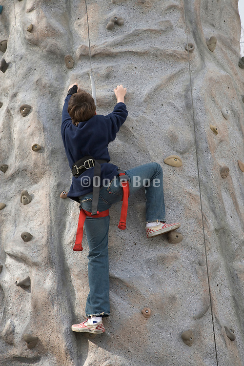 teenager climbing a climbing wall