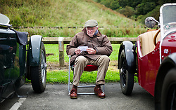 © Licensed to London News Pictures. <br /> 10/09/2017 <br /> Saltburn by the Sea, UK.  <br /> <br /> An owner sits between cars and reads the event programme during the annual Saltburn by the Sea Historic Gathering and Hill Climb event. Organised by Middlesbrough and District Motor Club the event brings together owners of a wide range of classic cars and motorcycles dating from the early 1900's to 1975. Participants take part in a hill climb to test their machines up a steep hill near the town. Once held as a competitive gathering a change in road regulations forced the hill climb to become a non-competitive event.<br /> <br /> Photo credit: Ian Forsyth/LNP