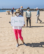 Locals Standing on the Beach with Face Masks and an Open Up Sign