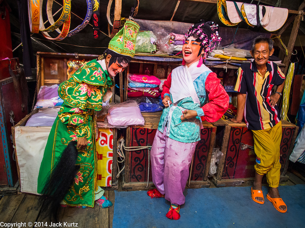 """18 AUGUST 2014 - BANGKOK, THAILAND:      Members of the Lehigh Leng Kaitoung Opera troupe joke backstage during a performance at Chaomae Thapthim Shrine, a small Chinese shrine in a working class neighborhood of Bangkok. The performance was for Ghost Month. Chinese opera was once very popular in Thailand, where it is called """"Ngiew."""" It is usually performed in the Teochew language. Millions of Chinese emigrated to Thailand (then Siam) in the 18th and 19th centuries and brought their culture with them. Recently the popularity of ngiew has faded as people turn to performances of opera on DVD or movies. There are still as many 30 Chinese opera troupes left in Bangkok and its environs. They are especially busy during Chinese New Year and Chinese holiday when they travel from Chinese temple to Chinese temple performing on stages they put up in streets near the temple, sometimes sleeping on hammocks they sling under their stage. Most of the Chinese operas from Bangkok travel to Malaysia for Ghost Month, leaving just a few to perform in Bangkok.   PHOTO BY JACK KURTZ"""