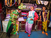 "18 AUGUST 2014 - BANGKOK, THAILAND:      Members of the Lehigh Leng Kaitoung Opera troupe joke backstage during a performance at Chaomae Thapthim Shrine, a small Chinese shrine in a working class neighborhood of Bangkok. The performance was for Ghost Month. Chinese opera was once very popular in Thailand, where it is called ""Ngiew."" It is usually performed in the Teochew language. Millions of Chinese emigrated to Thailand (then Siam) in the 18th and 19th centuries and brought their culture with them. Recently the popularity of ngiew has faded as people turn to performances of opera on DVD or movies. There are still as many 30 Chinese opera troupes left in Bangkok and its environs. They are especially busy during Chinese New Year and Chinese holiday when they travel from Chinese temple to Chinese temple performing on stages they put up in streets near the temple, sometimes sleeping on hammocks they sling under their stage. Most of the Chinese operas from Bangkok travel to Malaysia for Ghost Month, leaving just a few to perform in Bangkok.   PHOTO BY JACK KURTZ"