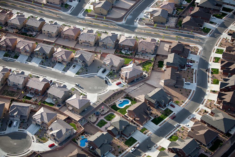 Suburban developments made up of predominantly adobe houses with fenced-in properties