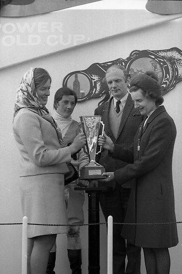 """The 'Powers' Gold Cup, Fairyhouse..1971..13.04.1971..04.13.1971..13th April 1971..The Running of the 'Powers' Gold Cup,sponsored by Irish Distillers, was run today at Fairyhouse, Co Meath..The race was won by 'Glending""""ridden by John Donaghy. The horse is owned by Mr J.W.Osborne and trained by Mr P.D.Osborne..Photograph of Mrs Frank J O'Reilly,wife of the Chairman of Irish Distillers, presenting the Gold Cup to      Mrs P.D.Osborne,wife of the trainer. Included in the photograph are, jockey, John Donaghy and P.D.Osborne the trainer of 'Glending'."""