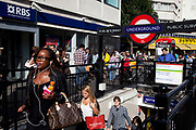 Scene outside Notting Hill underground station exit, West London, UK. This is classic London with busy crowds of people coming to hang out at Portobello Road.