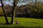 Woman meditating in the afternoon sun in Waterlow park during the Coronavirus pandemic on 27th March 2020 in London, United Kingdom. Social distancing measures like this are steps taken to reduce social interaction between people to help reduce the transmission of coronavirus COVID-19.