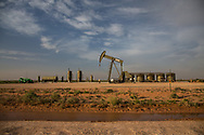 Active pump jack next to storage tanks in Eddy County New Mexico . Eddy County's oil patch in the Permian Basin is experiencing an oil boom due to the fracking industry.
