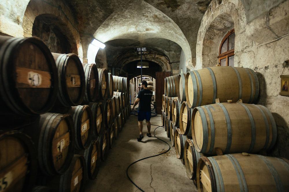 Adam Kassis, head winemaker of Latrun Monastery Winery, is seen walking between oak barrlels in an underground chamber at the winery, west of Jerusalem, Israel, on August 11, 2018.
