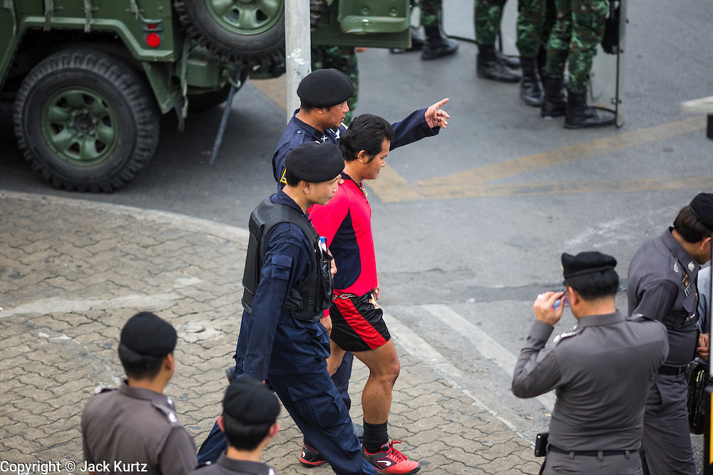 29 MAY 2014 - BANGKOK, THAILAND: Thai police lead away a suspected member of the Red Shirts, a group that supports the elected civilian government and opposed the coup. After a series of protests around Victory Monument earlier in the week, the Thai army Thursday shut down vehicle access to the area, one of the main intersections in Bangkok, and kept people out of the area. Thousands of soldiers surrounded the Monument and effectively locked the area down. There were no protests at Victory Monument for the first time in the week since the coup deposed the elected civilian government.   PHOTO BY JACK KURTZ