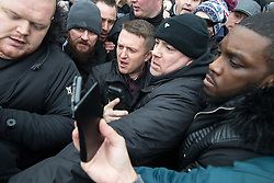 """© Licensed to London News Pictures . 18/03/2018 . London , UK . TOMMY ROBINSON (centre) pushes his way from the crowd to leave after delivering his speech . 1000s including supports of alt-right groups such as Generation Identity and the Football Lads Alliance , at Speakers' Corner in Hyde Park where Tommy Robinson reads a speech by Generation Identity campaigner Martin Sellner . Along with Brittany Pettibone , Sellner was due to deliver the speech last week but the pair were arrested and detained by police when they arrived in the UK , forcing them to cancel an appearance at a UKIP """" Young Independence """" youth event , which in turn was reportedly cancelled amid security concerns . Photo credit: Joel Goodman/LNP"""