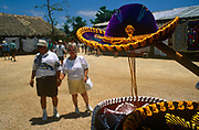 Tourists explore tourist sombrero trinket shops during their cruise ship excursion at Chaccoben Mayan ruins. Having disembarked from a Carnival Cruise ship at the port of Cancun, Mexico two excursion tourists walk towards a shop rack of the tacky Mexican hats, displayed under a tropical sun at the archaeological ruins of Chaccoben, Yukatan. Stitched with yellow edging and with a velvet top, the hats are prized by Americans on once in a lifetime vacations.